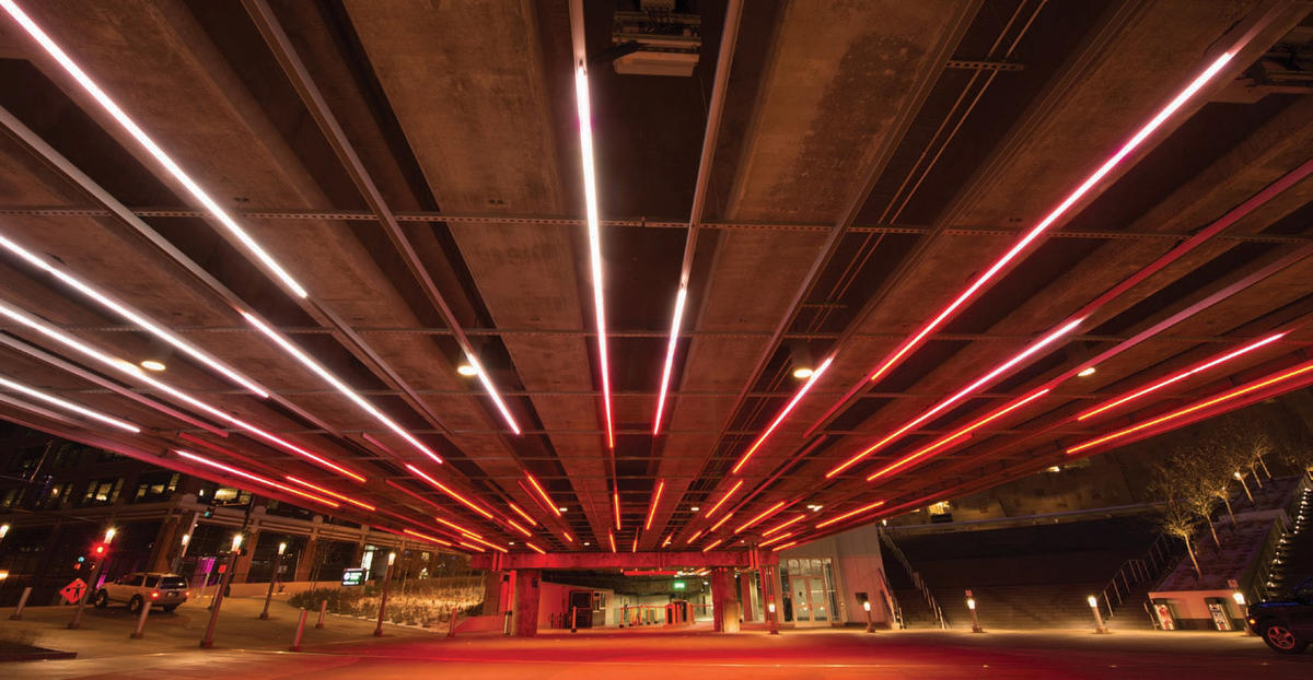 "When entering the underpass the color-changing lighting effects provide a dynamic display. There are also lighting fixtures under benches (below) to provide a soft glow for adjacent walking surfaces, which gives the paths a ""romantic"" feel in contrast to the underpass lighting."